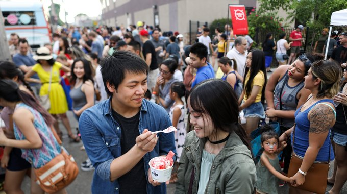 After waiting more than forty-five minutes to buy Thai rolled ice cream from SOTA Hot & Cold's Night Market stand, customers Tou and Molly enjoy a spoonful of the frozen dessert.