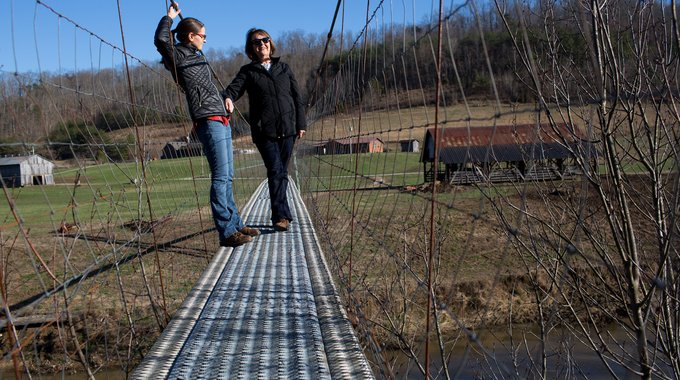 """Stay in Clay"", a nonprofit in Clay County, Kentucky and part of the Berea BCJI initiative, has organized volunteers to restore traditional swinging bridges throughout the county. Stay in Clay aims to inspire residents, especially youth, to take pride in their region and its culture. Jenna Meglen, left, of Berea College, and Vanda Rice, president of Stay in Clay, stand on a refurbished bridge."