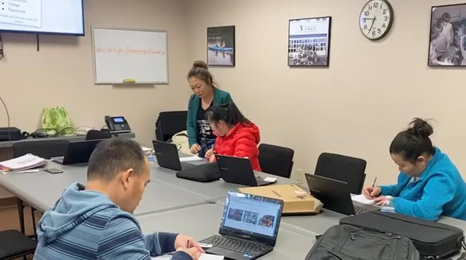 LISC AmeriCorps member Mai Kou Yang, standing, coaching CAP Services clients in a computer skills class at Stevens Point, Wisconsin. Yang, her family and her Hmong community have been connected with CAP Services since she was a child.