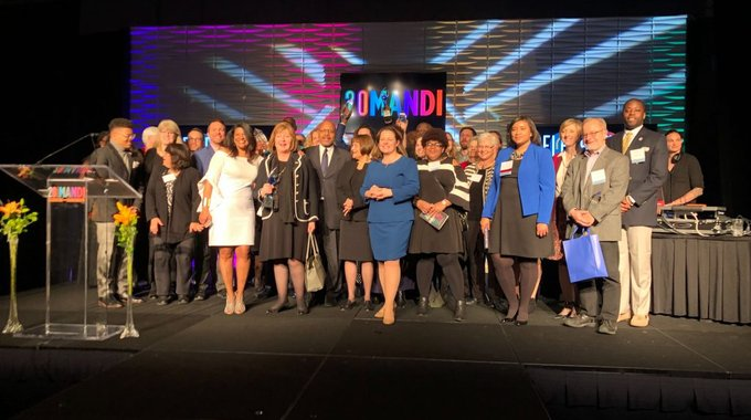 The 20th Anniversary MANDI finalists pose with Donsia Strong Hill & LISC's CEO Maurice Jones on stage following the awards. 