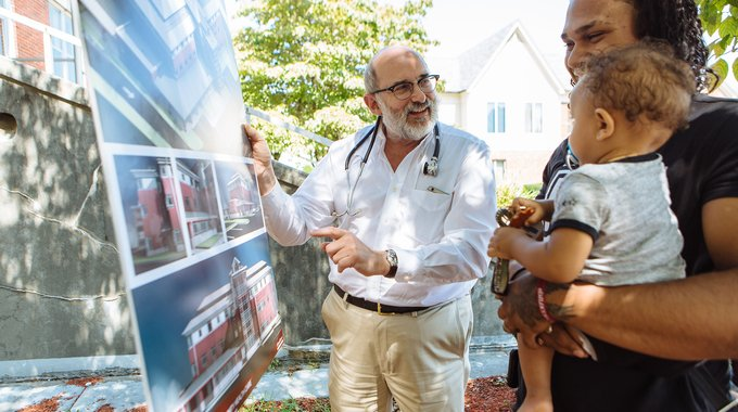 "Dr. Michael Fine, a member of the Central Falls Health Equity Zone collaborative and former director of the Rhode Island Department of Health, shares a rendering of the new neighborhood ""health station"" with residents."