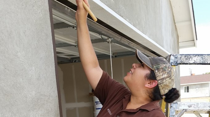 "Natali Gonzalez paints the garage door trim, in the final phases of constructing her home with Community Housing Improvement Project, a longtime LISC partner. ""I didn't realize how much this was going to mean,"" she says. ""It was like having another baby."""
