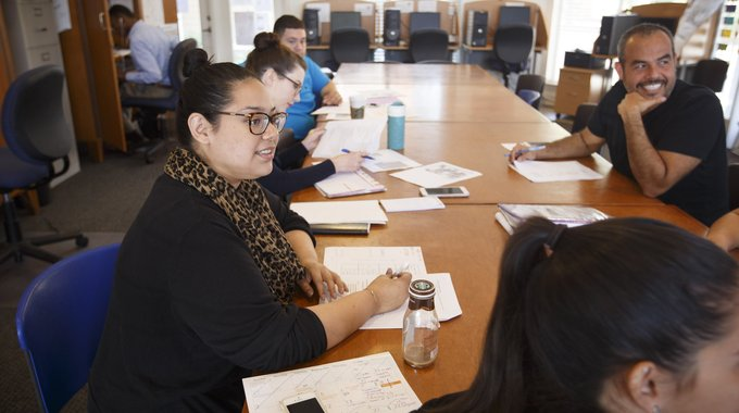 Angela Guerrero (at left), an Avenue CDC organizer, meeting with colleagues. Guerrero got interested in community development after her grandmother's house, where she grew up, was repaired by a LISC and Avenue partner. That led to an internship, which led to a career.