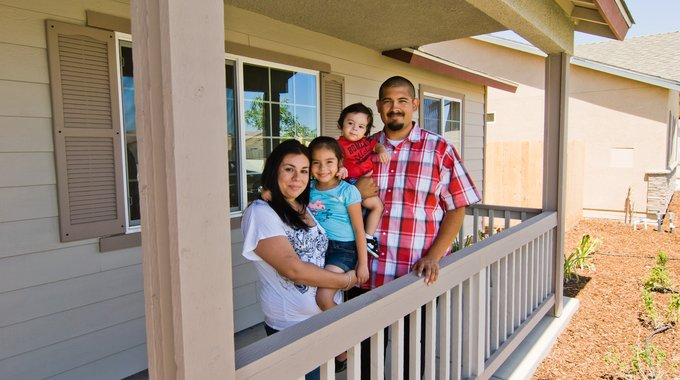 A family on the porch of their house, built through Self-Help Enterprises, in rural California.